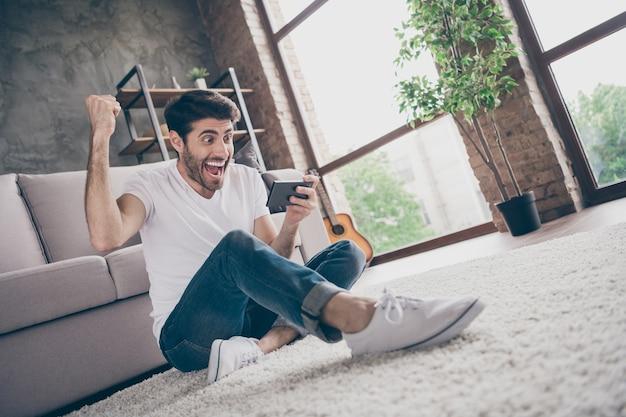 Ура! фотография сумасшедшего парня смешанной расы, сидящего на полу, опирающегося на диван, с телефоном и чтения неожиданных позитивных новостей подписчики блога носят повседневную одежду в гостиной на чердаке