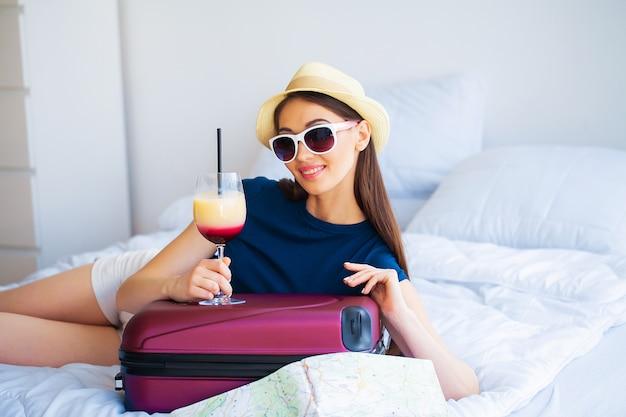 カクテルとhootelルームのベッドの上のスーツケースと美しい女性