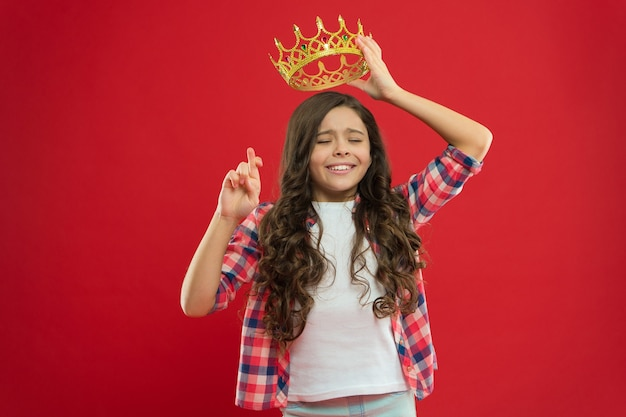Hope for the best. kid hold golden crown symbol of princess. childhood concept. every girl dreaming to become princess. girl cute baby hold crown while stand red background. lady little princess.
