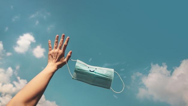 Надежда, позитивный настрой на концепцию коронавируса. рука подняла улыбающуюся медицинскую маску в голубое небо. жест означает до свидания. глубокое дыхание свежим воздухом