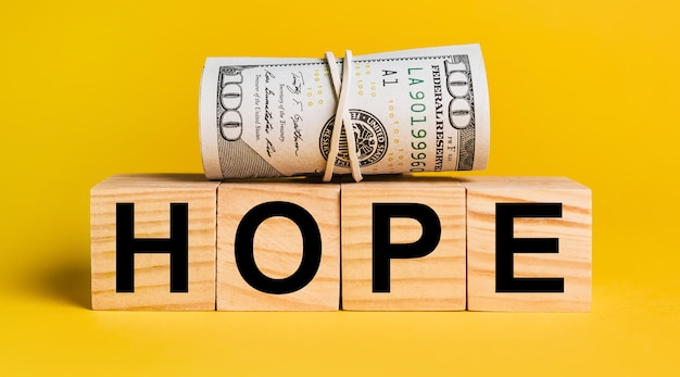 Hope with money on a yellow background. the concept of business, finance, credit, income, savings, investments, exchange, tax