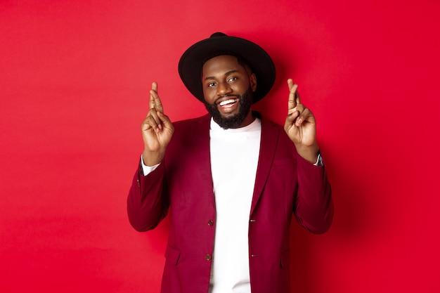 Speranzoso uomo afroamericano che esprime desiderio, tenendo le dita incrociate per buona fortuna e sorridendo ottimista, in piedi sullo sfondo del partito rosso
