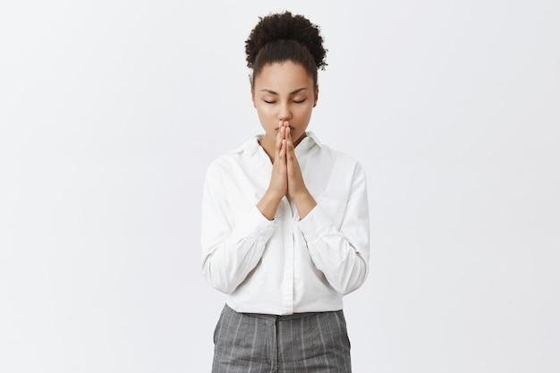 希望に満ちたアフリカ系アメリカ人の女性が祈ったり、懇願したり、願い事をしたりする