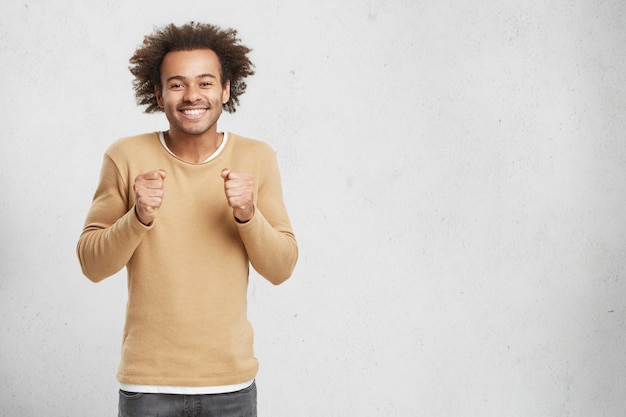 Hopeful afro american male keeps hands in fists, smiles happily as waits for important decision