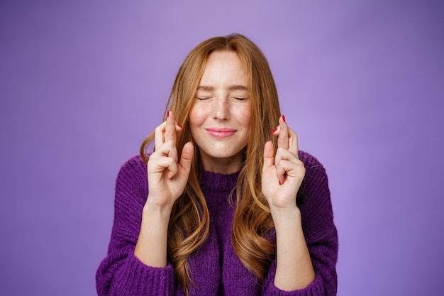 Обнадеживающая и мечтательная милая, нежная рыжая девушка 20-х годов в фиолетовом свитере загадывает желание, искренне закрывая глаза и скрещивая пальцы на удачу, поскольку в предвкушении чуда происходит чудо, молящая над фиолетовой стеной.