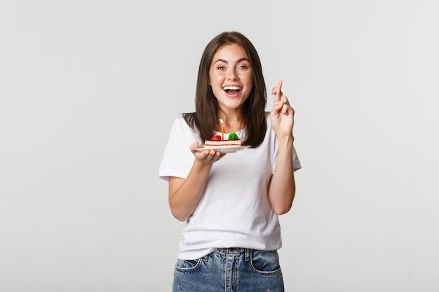 希望に満ちた幸せな笑顔の誕生日の女の子は、b-dayケーキにろうそくを吹きながら指を交差させて願い事をします。