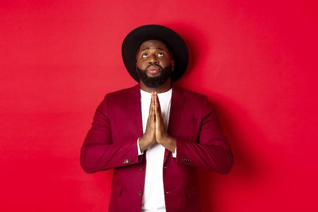 希望に満ちた悲しい黒人男性が神に話しかけ、手をつないで祈り、見上げ、懇願し、助けを求め、赤い背景に立ちます。
