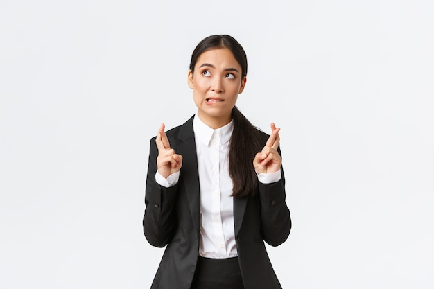 Hopeful asian businesswoman looking worried, biting lip and cross fingers good luck, making wish, anticipating big contract or deal, worried about outcome, standing white background
