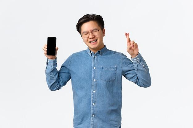 Speranzoso ragazzo asiatico con bretelle chiudi gli occhi e incrocia le dita buona fortuna mostrando lo schermo dello smartphone aspetta...