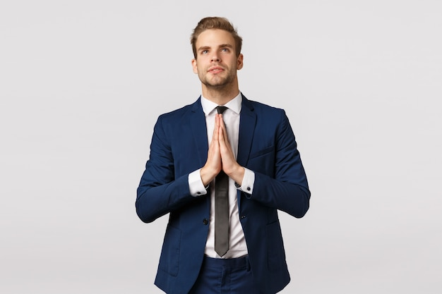 Hopeful attractive blond caucasian guy, male entrepreneur in classic suit, business formal wear, hold hands together in pray, look up sky like believer, praying, making wish