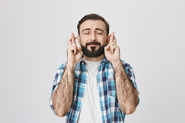 Speranzoso uomo adulto barbuto che esprime desiderio, incrociare le dita e chiudere gli occhi
