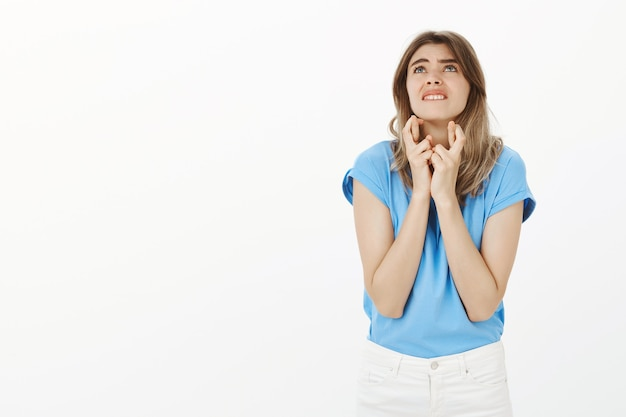 Обнадеживающая белокурая женщина скрестит пальцы удачи, загадывает желание, молится