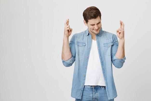 Speranzoso ragazzo bruna incrocia le dita, pregando o esprimendo un desiderio