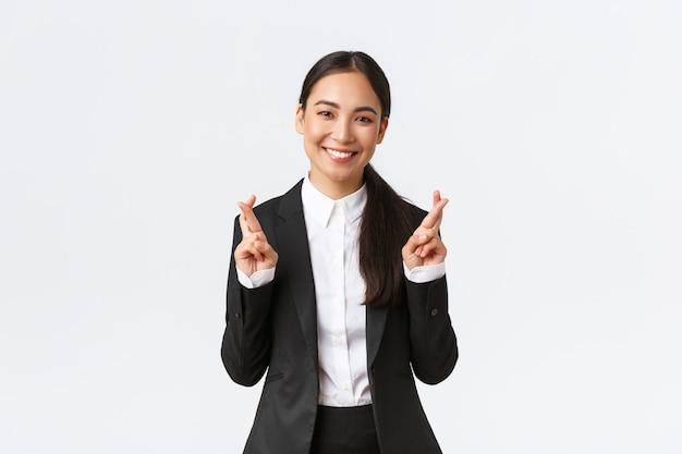 有望な結果を待っている希望に満ちた実業家、幸運を交差させ、楽観的な笑顔。願い事をし、良いニュース、白い背景を期待して黒いスーツの幸せなセールスウーマン