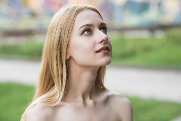 Hopeful caucasian woman standing outside looking at sky in contemplation