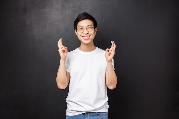 Hopeful charismatic asian guy hoping deal go well, cross fingers good luck and smiling optimistic, praying, making wish, anticipating good news, pleading over