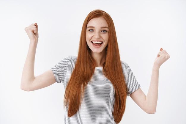 Speranzoso affascinante attraente bella rossa giovane ragazza occhi azzurri tifo alzando i pugni alta felicità felice, soddisfatto buon risultato festeggiare il punteggio, trionfare con gioia, muro bianco