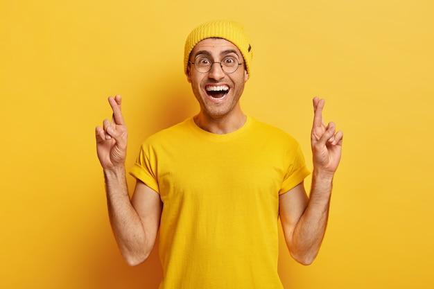Hopeful cheerful guy crosses fingers for good luck