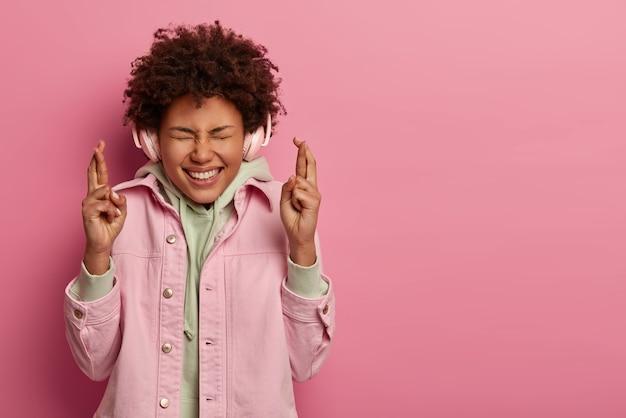희망을 품은 쾌활한 여성이 행운을 위해 손가락을 교차하고 긍정적으로 킥킥 웃습니다.