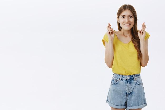 Speranzosa ragazza carina che sembra preoccupata e nervosa, esprimendo il desiderio con le dita incrociate
