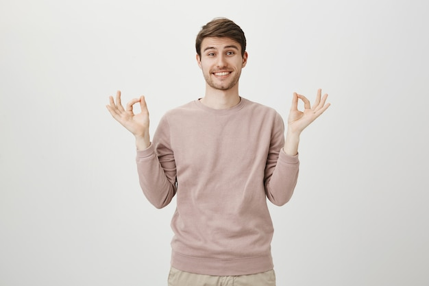 Обнадеживающий милый молодой человек показывает хорошо, жест дзен