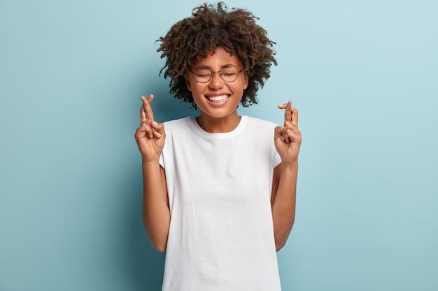 이빨 밝은 미소를 지닌 희망적 어두운 피부의 여성, 흰색 티셔츠를 입고 행운을 믿고 아프로 헤어 스타일을 가지고 있으며 꿈이 이루어지기를 희망하며 파란색 벽 위에 고립되어 있습니다. 제발, 하나님이 도와주세요!