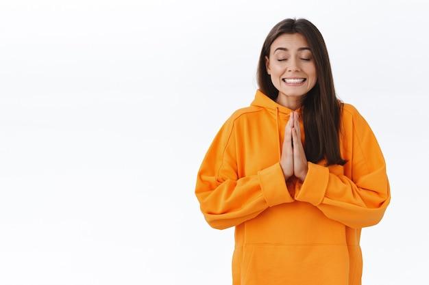 オレンジ色のパーカーを着た希望に満ちた夢のような魅力的な女の子、目を閉じて楽観的な笑顔、胸の近くで一緒に押して祈って手をつないで、夢の実現を懇願し、願い事をし、白い壁