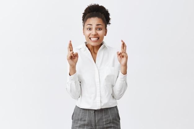 La donna di affari afroamericana speranzosa ed eccitata incrocia le dita, buona fortuna, esprimendo il desiderio