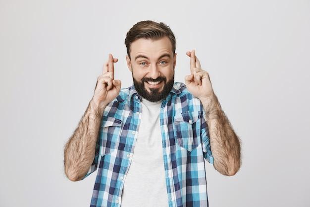 Speranzoso ragazzo barbuto eccitato incrocia le dita, pregando