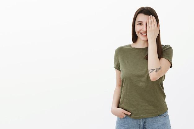 Giovane brunetta europea fiduciosa ed eccitata di anni '20 con occhio di copertura del tatuaggio e metà del viso sorridendo ampiamente sbirciando felice