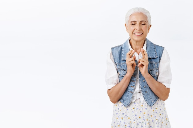 Hopeful, faithful happy senior woman with combed grey hair, wear trendy denim vest, dress, close eyes and smiling as dreaming, imaging dream came true, cross finger good luck, praying