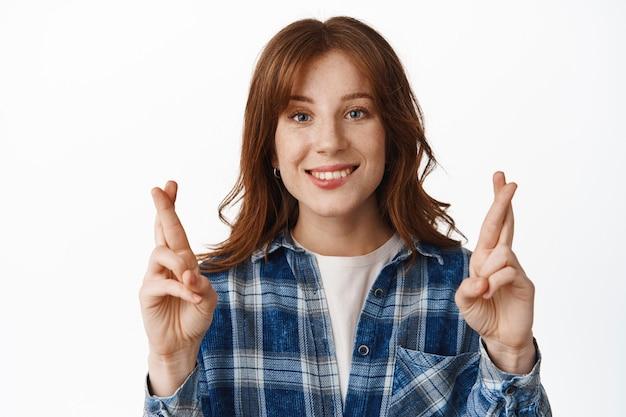생강 머리와 주근깨가 있는 희망적인 여학생, 행복하게 웃고 흰색으로 소원을 빌다