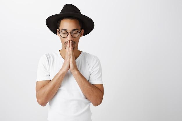 Обнадеживающий красивый афро-американский молодой человек, взявшись за руки в молитве, умоляя или прося, пожалуйста