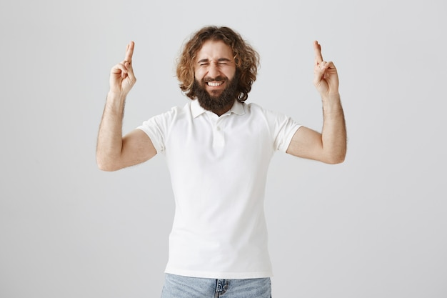 希望に満ちた幸せな中東の男が指を組んで願い事をしている