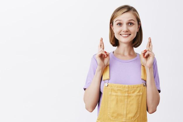 希望に満ちた幸せな若い女性は、幸運を祈り、笑顔で指を交差させます