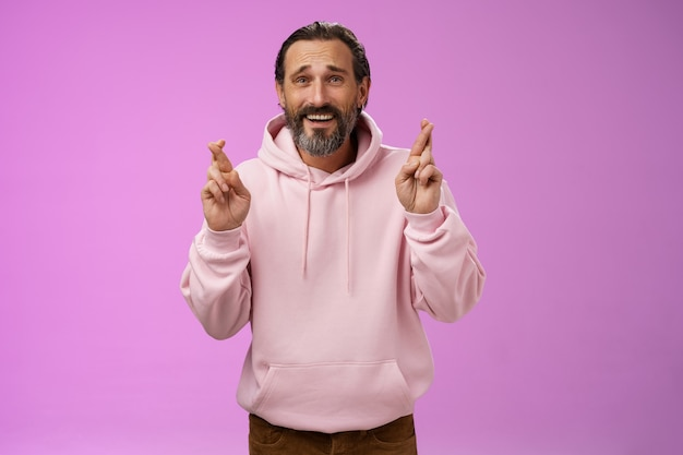 Hopeful lucky optimistic worried mature stylish bearded man grey hair in trendy hoodie cross fingers wish anticipating important results nervously standing purple background frowning anxious.
