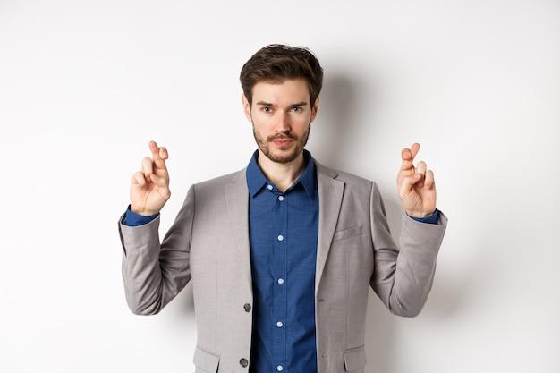 Обнадеживающий мужчина в костюме скрещивает пальцы на удачу и выглядит уверенным в победе, чувствуя решимость, стоя на белом фоне.