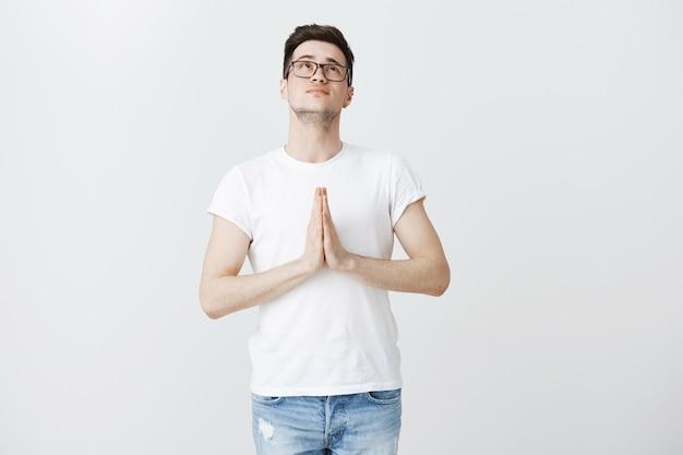 Uomo pieno di speranza che supplica dio, guarda in alto e prega