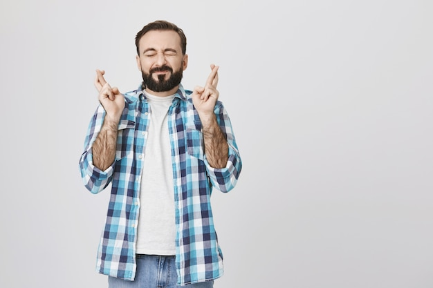 Hopeful middle-aged man making wish with fingers crossed