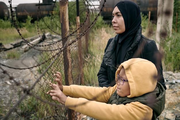 히잡을 쓴 희망적인 이슬람 여성이 철조망에 딸과 함께 서서 먼 곳을 바라보고 있다