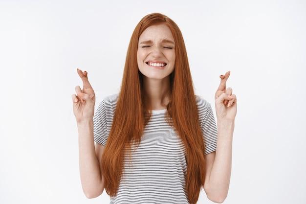 희망적 긴장 귀여운 빨간 머리 소녀 높은 희망 물린 아랫입술 십자가 손가락 행운을 빌다 소원 중요한 결과를 기대하는 희망 승리 서있는 흥분 흰 벽 기적을 믿습니다