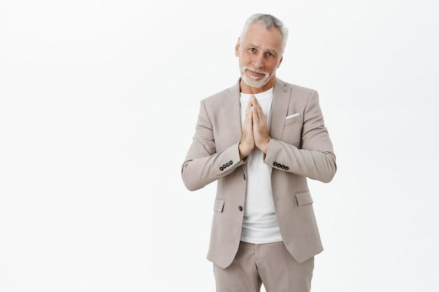 Обнадеживающий старик в костюме просит милостыню, взявшись за руки в молитве