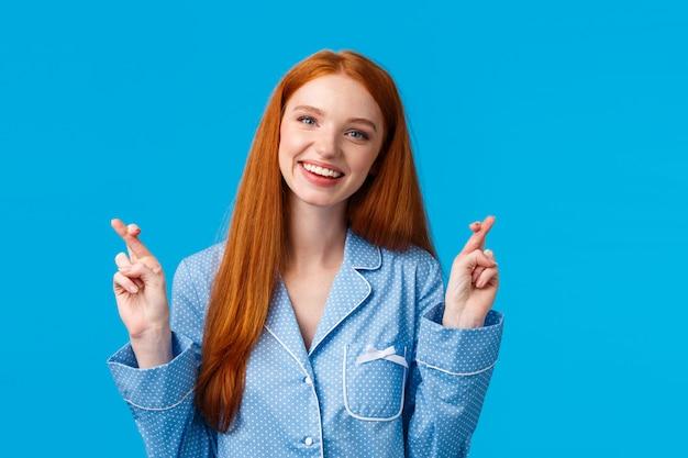 Hopeful optimistic cute redhead girl in nightwear, cross fingers good luck, tilt head