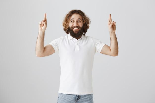 希望に満ちた楽観的な中東の男が指を交差させて願い事をする