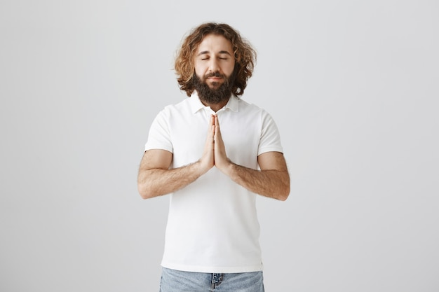 Hopeful peaceful middle-eastern man praying, making wish, holding hands in plead gesture