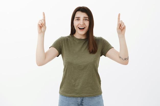 Speranzosa e contenta sorpresa attraente giovane donna di 20 anni con occhi marroni e tatuaggio che sorride dallo stupore e dalla gioia e indica il prodotto fantastico reagendo deliziata e impressionata sul muro grigio