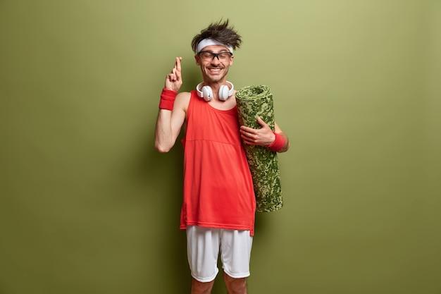 Надеющийся и позитивный мужчина скрещивает пальцы и верит в успешные тренировки, готовится к тренировке, держит каремат, носит спортивную одежду, имеет веселое выражение лица, изолированного на зеленой стене. время для спорта