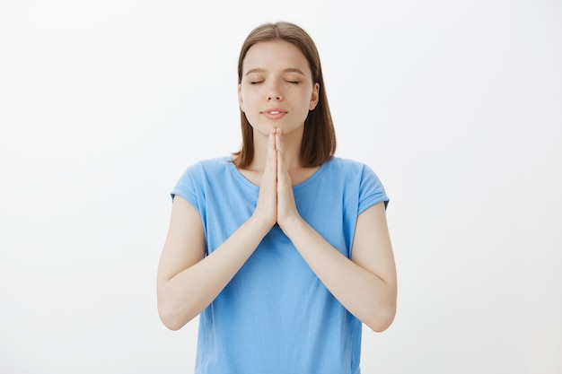 Hopeful praying woman clasp hands together, pleading or making wish