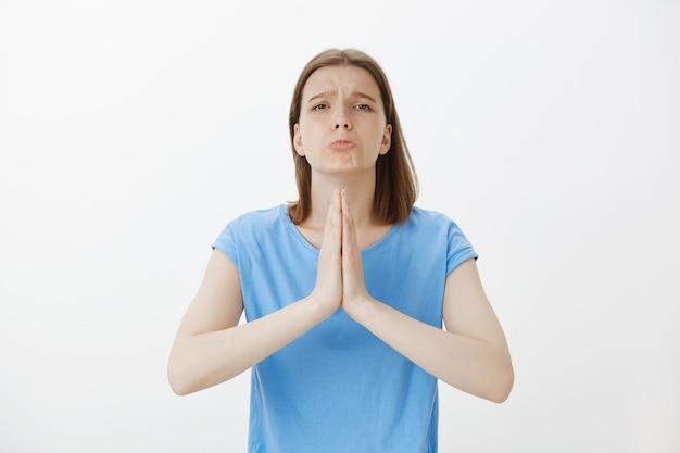 Обнадеживающая молящаяся женщина сцепляет руки вместе, умоляя или загадывая желание