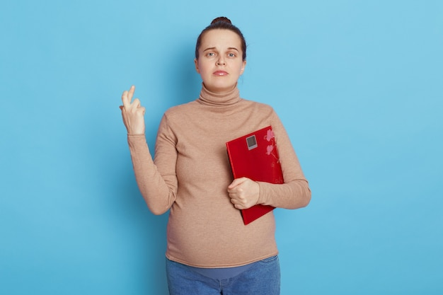 Hopeful pregnant woman crossing fingers and looks at camera holding a scale isolated over blue wall.